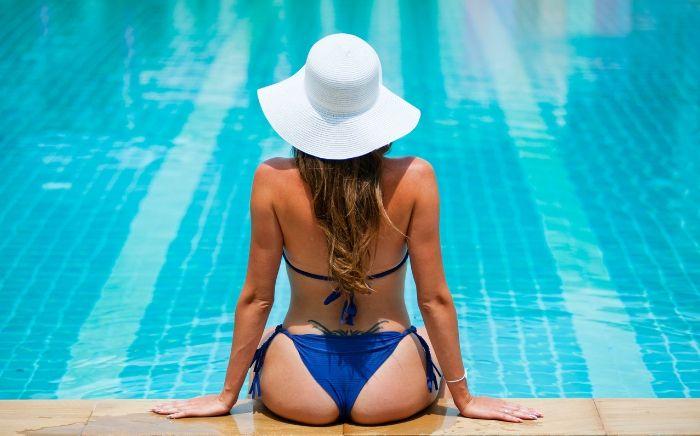 水着を着てプールを眺める女性の後ろ姿
