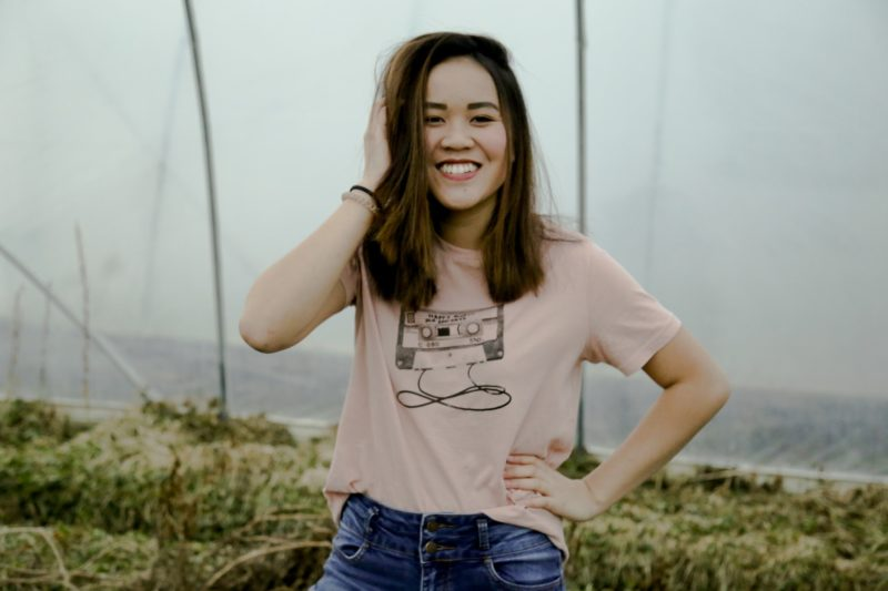 頭に手を当てて笑うアジア人女性