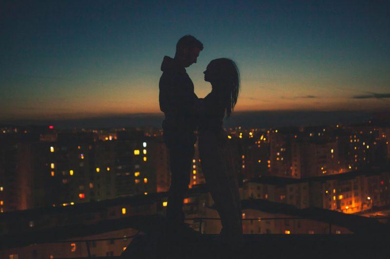 夜景をバックに見つめ合うカップル